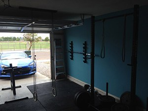 A Garage Gym Preventing A Car From Entering, But Only Temporarily. Stylish And Organized.