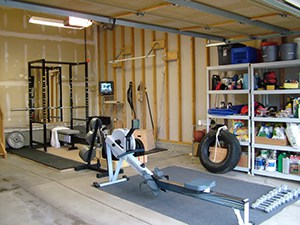 Cardio Packed Home Gym With A Tire And Power Rack. Shelves On The Side Keep All The Miscellaneous Stuff Out Of The Way,