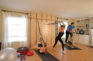 Family Fun In This House Gym With Wall Mounted Stretch Bands As Well As An Elliptical Machine And Yoga Mats.