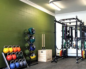 Filled With Colorful And Heavy Kettle Bells And Wall Balls. Neat Looking Compact Garage Gym With Green Walls.