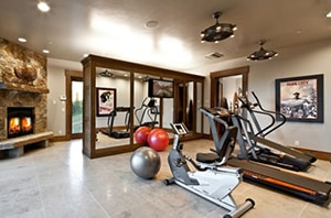 Gym In The House With A Fireplace, Stability Ball, And Cardio Machines Such As Treadmill And Cycling.