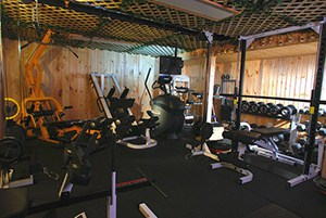 Home Gym Idea Wooden Panneling, Very Dim And Slick Looking. Gym Equipment Everywhere For All Purposes.