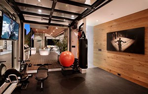 Home Gym With A Punching Bag, Weight Bench, And A Cool Looking Poster Of A Boxer In A Ring Corner. We Want One.