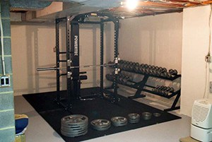 Organized Garage Gym Weights Set. Barbell Just Chilling On The Squat Rack, Waiting To Get Pumped. Air Purifier On The Side.