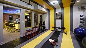 Pretty Sweet Garage Gym With Yellow Stripes And A Bar For Relaxation On The Opposite Side. Stylish And Clean.