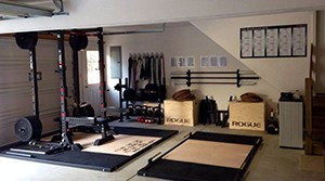 Rogue Fitness Themed Super Strength Training Home Gym With Thick Pads. Exercise Poster On The Wall Is A Nice Touch.