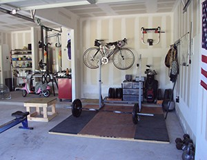 Thick Garage Gym Flooring And A Great Idea To Hang The Bike Up. Easy To Clean And Let The Car In Too.