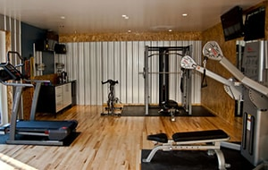 Very Fancy Looking Wooden Floor Home Gym With Workout Machines And A Treadmill.