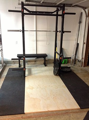 Very Simple Power Rack With A Flat Weight Bench In The Background. All You Need Is Those Barbells In The Background And Some Weights.