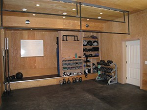 Wooden Crossfit Garage Gym Theme, Organized And Clean Looking With Barbells And Dumbbells.