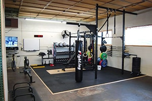 Yet Another Mixed Martial Arts Themed Garage Gym. Dip Bars And Lots Of Dumbbells As Well. Obligatory Tv In The Background To Watch Ufc.