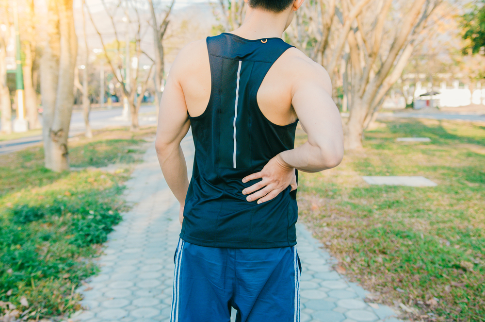 guy on jog holding his lower back in pain