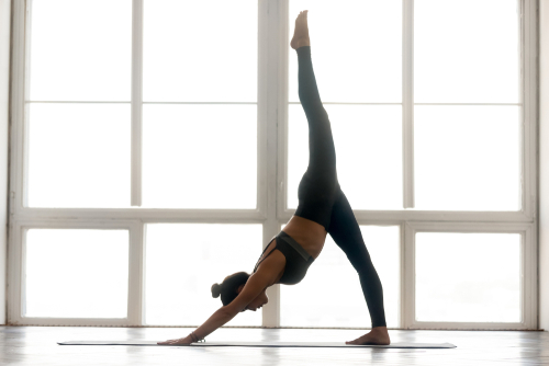 woman doing downward dog split yoga pose