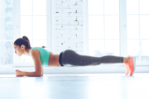 woman doing the plank in a yoga studi