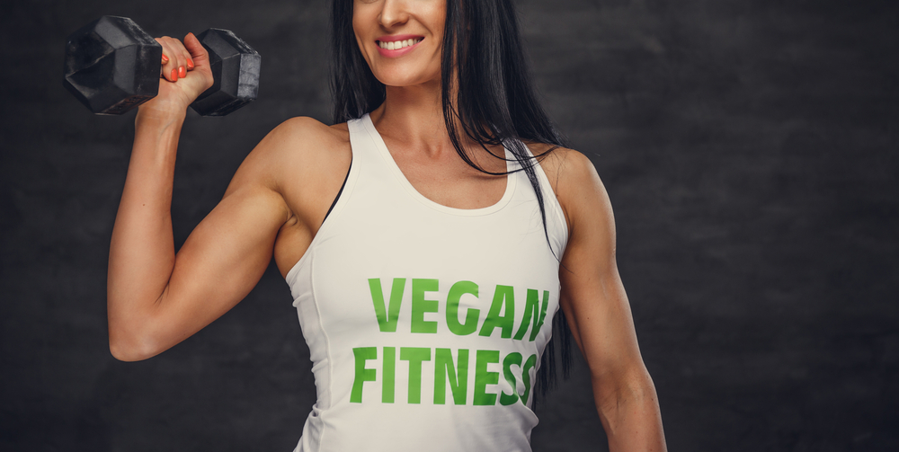 woman lifting dumbbell wearing vegan fitness t-shirt