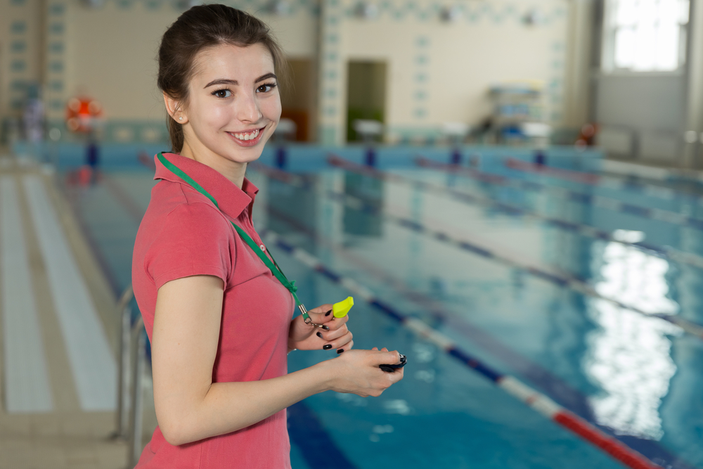 swimming coach happy with a whistle in her hand