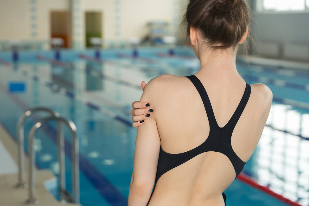 girl holding her shoulder in pain in front of a swimming pool
