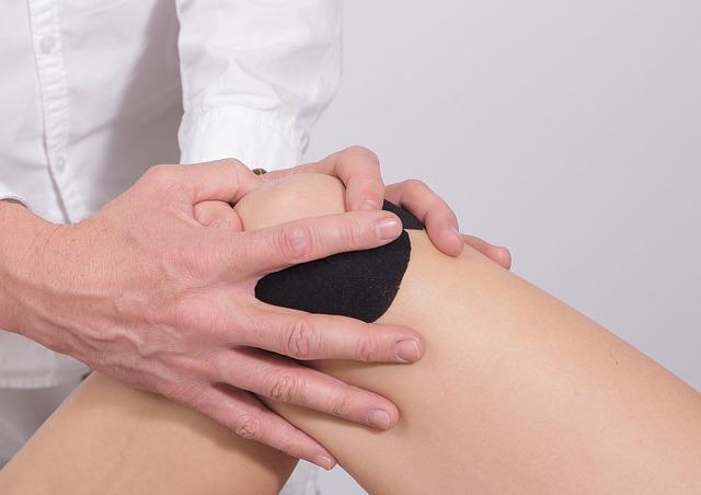 doctor adjusting a patients knee
