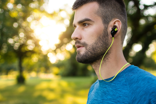 fit man running with bluetooth earbuds