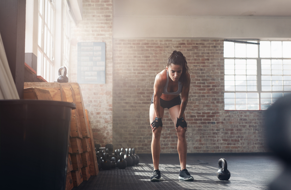 young fit woman doing crossfit and holding her knees