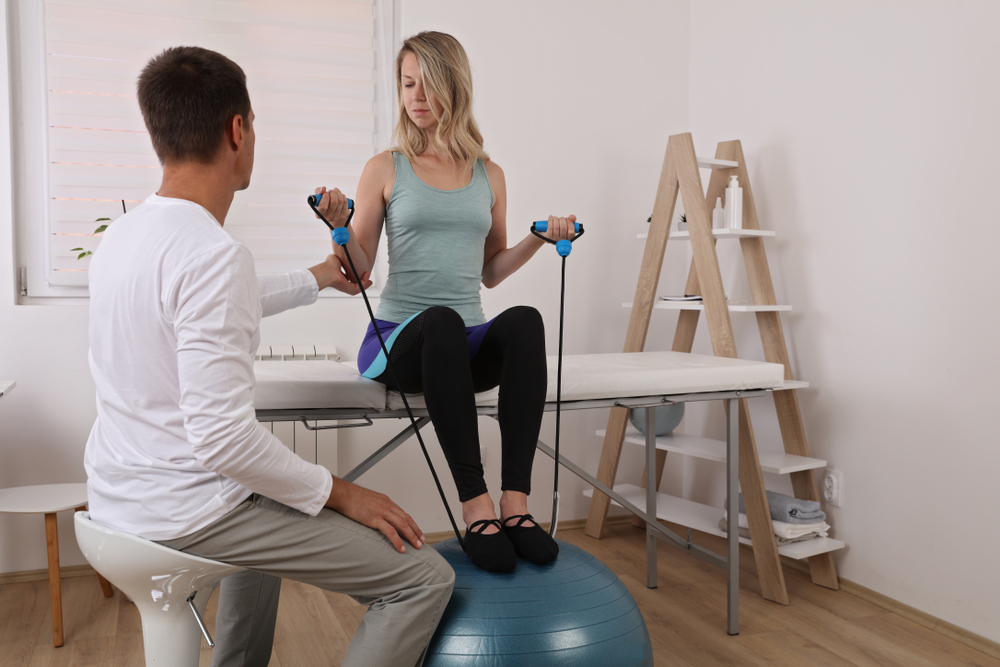 injured woman working out on an exercise ball with bands