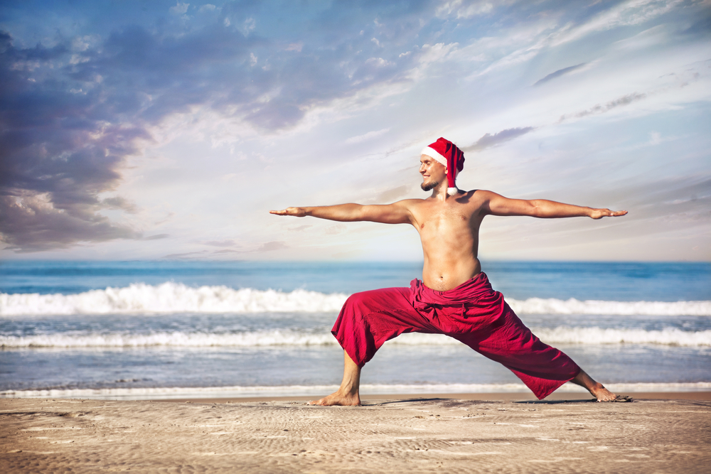 shirtless fit guy on a beach doing yoga and wearing a santa hat